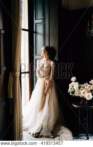Bride Is Leaning Against The Frame Of The Large Window Of An Old Villa And Looks Out Into The Courty