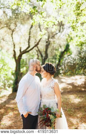 The Bride And Groom With A Bouquet Stand Hugging Among The Trees In An Olive Grove, The Groom Kisses