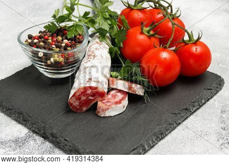 Sliced Salami Sausage On The Black Stone Board With Tomatoes, Peppers, Dill And Parsley At The Backg
