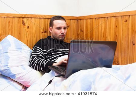 Man With Laptop In Bed