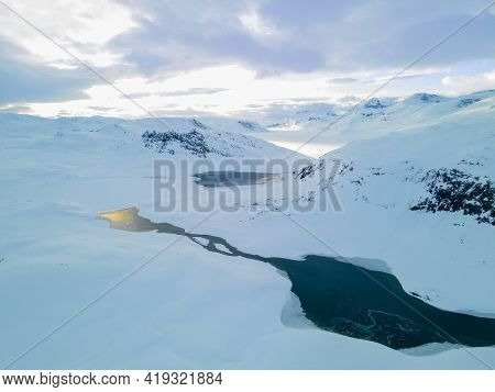 Stunning Aerial View Of A River Flowing Through A Snow Covered Tundra.