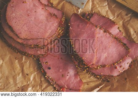 Delicious peppered roast beef pastrami slices on paper with grains of coloured pepper