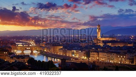 Florence, Italy. Sunset panorama. Evening view at ancient city and famous Ponte Vecchio bridge on river Arno with picturesque clouds on sky and Bell tower on the horizon.