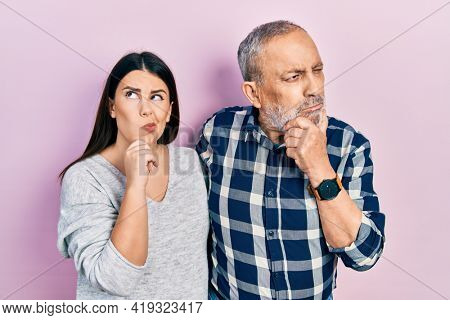 Hispanic father and daughter wearing casual clothes thinking worried about a question, concerned and nervous with hand on chin