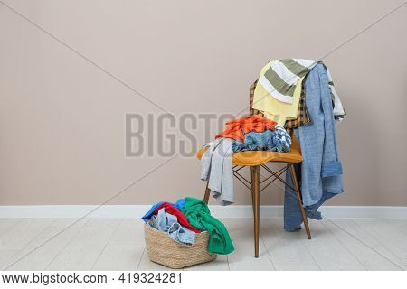 Orange Chair And Wicker Basket With Different Clothes Near Light Grey Wall, Space For Text
