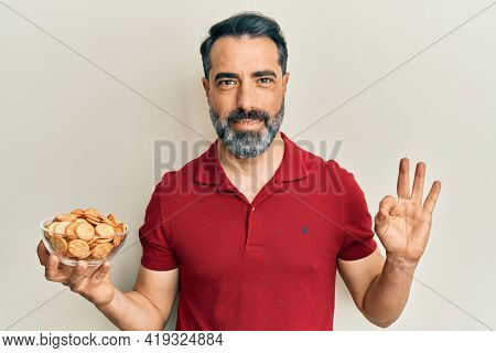 Middle age man with beard and grey hair holding bowl with salty crackers biscuits doing ok sign with fingers, smiling friendly gesturing excellent symbol