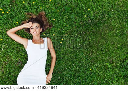 Woman in white dress lying on green grass in the garden. Top view.