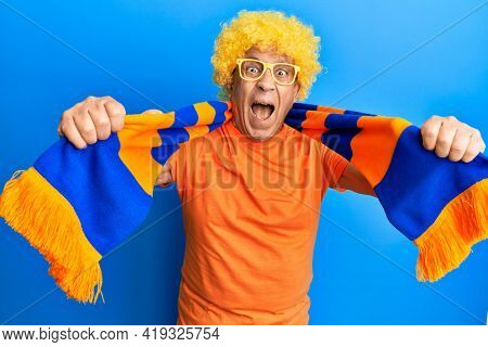 Senior hispanic man football hooligan cheering game celebrating crazy and amazed for success with open eyes screaming excited.