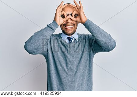 Hispanic adult man wearing glasses and business style doing ok gesture like binoculars sticking tongue out, eyes looking through fingers. crazy expression.