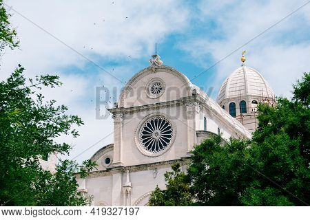 View Of The Cathedral Of St. James In Sibenik, Croatia Against The Background Of Blue Sky And Green