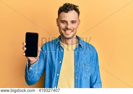 Young hispanic man holding smartphone showing blank screen looking positive and happy standing and smiling with a confident smile showing teeth