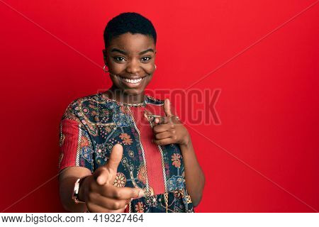 Young african american woman wearing african style pointing fingers to camera with happy and funny face. good energy and vibes.