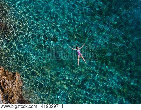 Aerial View Of The Young Female Floating On The Back And Relaxing On The Warm Turquoise Adriatic Sea
