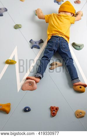 A Child In Jeans And A Yellow T-shirt Resolutely Climbs Up The Climbing Wall. Climbing Wall In The F