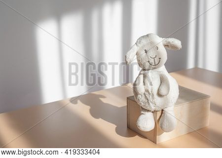 Lonely Children's Toy Plush White Lamb Sitting On Wooden Stand On Background Of White Wall With Shad