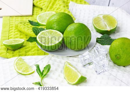 Fresh Green Juicy Limes And Lime Slices With Mint Leaves In The Kitchen On Light Background.