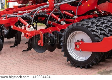 Agriculture Equipment For Soil Cultivation. Close Up View Of New Red Tractor Plow For Land Cultivati