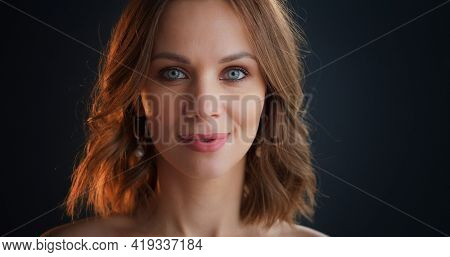 Portrait of young caucasian woman on dark background