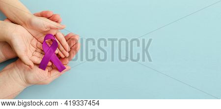 National Cancer Survivors Day. Adult And Child Hands Holding Purple Ribbon On Blue Background. Alzhe
