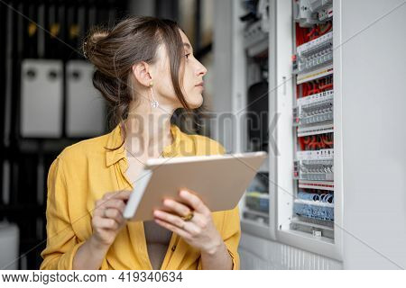 Young Housewife Monitors Performance Of Household Expences On A Digital Tablet, Standing In The Boil