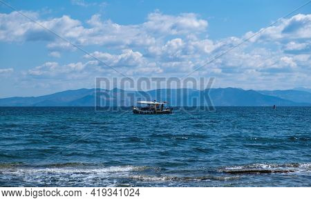 Traditional Fishing Boat Sailing In Rippled Sea Background. Blue And White Trawler In The Middle Of