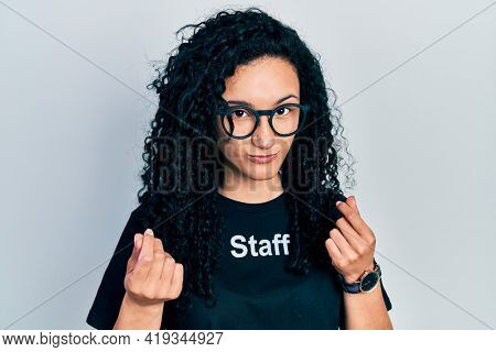 Young hispanic woman with curly hair wearing staff t shirt doing money gesture with hands, asking for salary payment, millionaire business