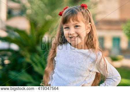 Adorable caucasian child girl  smiling happy standing at the city.