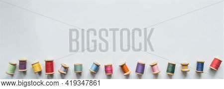 A Large Banner With Lots Of Multicolored Threads On Wooden Old-fashioned Reels On A White Background