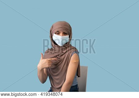 Immunized Teen Girl In Muslim Hijab Pointing Finger At Adhesive Plaster Bandage On Her Arm After Cor