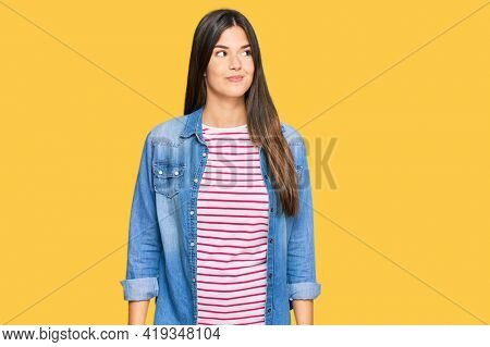Young brunette woman wearing casual clothes smiling looking to the side and staring away thinking.