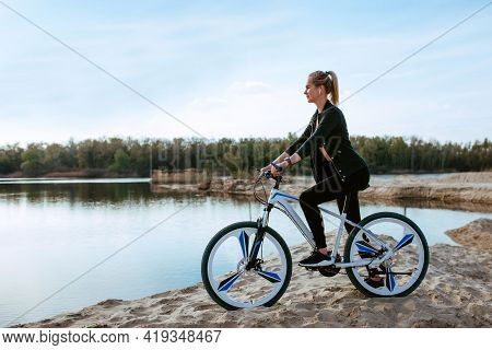 Beautiful Girl On A Bike On The Sand Near The River. Sport And Recreation Concept