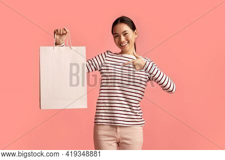 Sales And Consumerism Concept. Happy Asian Woman Pointing At Blank Shopping Bag,