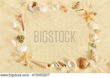 Frame Made Of Seashells And Starfishes On A Sand Background. Marine Summer Concept. Copy Space Betwe