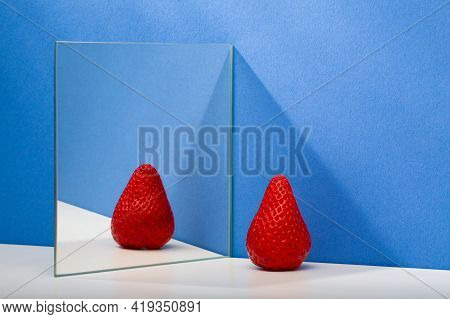 A Fresh And Tasty Strawberry Reflected In The Mirror On The Blue Background. Fresh Strawberry In The