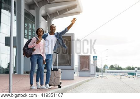Happy Young Black Couple Standing With Suitcases Near Airport Terminal, Catching Taxi