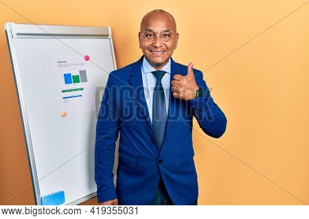 Middle age latin man wearing business clothes on chart presentation doing happy thumbs up gesture with hand. approving expression looking at the camera showing success.
