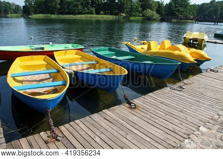 Bright Multicolored Boats And Catamarans At The Pier On A Sunny Summer Day. The Picture Was Taken At