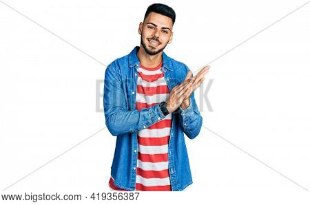Young hispanic man with beard wearing casual denim jacket clapping and applauding happy and joyful, smiling proud hands together