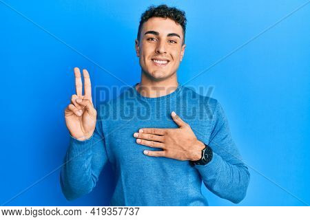 Hispanic young man wearing casual winter sweater smiling swearing with hand on chest and fingers up, making a loyalty promise oath