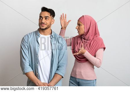 Misunderstanding In Relations. Young Muslim Couple Arguing, Woman In Hijab Blaming Husband