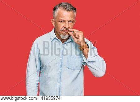 Middle age grey-haired man wearing casual clothes mouth and lips shut as zip with fingers. secret and silent, taboo talking