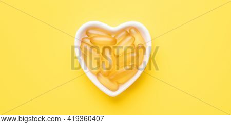 Horizontal Banner With Omega 3 Capsules In A Heart-shaped Plate On Yellow Background. Fish Oil Softg