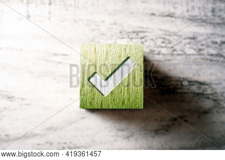 Check Mark On A Green Wooden Checkbox Block On A Table