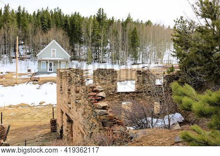 Remnants Of A Collapsing Historical Building Surrounded By A Pine And Aspen Forest With A Rustic Hom