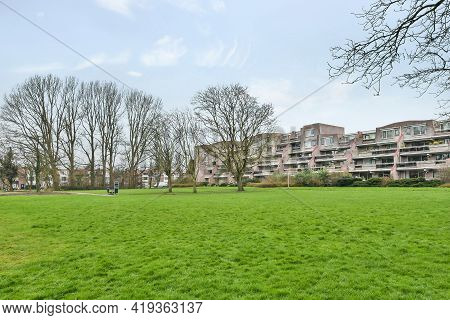 Low Rise Residential Building With Large Green Lawn In Front And Leafless Trees In Early Spring
