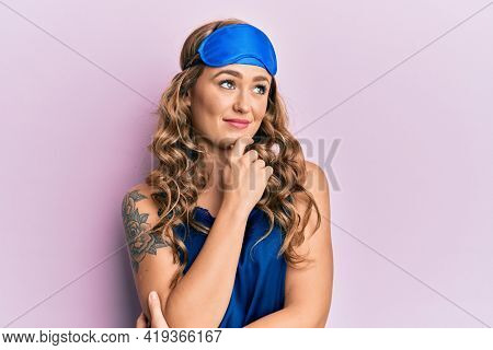 Young blonde girl wearing sleep mask and pyjama thinking concentrated about doubt with finger on chin and looking up wondering