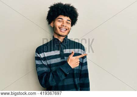Young african american man with afro hair wearing casual clothes cheerful with a smile of face pointing with hand and finger up to the side with happy and natural expression on face