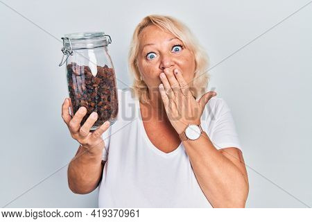 Middle age blonde woman holding raisins bowl covering mouth with hand, shocked and afraid for mistake. surprised expression