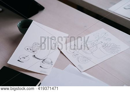 Sketches Lie On A White Wooden Table. Drawing A Liner. A Sketch Of A Future Illustration.