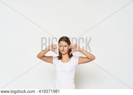 Woman In White T-shirt Shows Thumb Down Displeasure Emotion